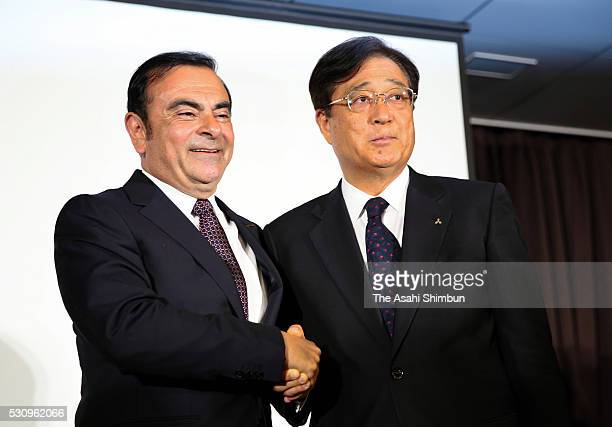 Nissan Motor Co President Carlos Ghosn and Mitsubishi Motors Chairman Osamu Masuko shake hands during a joint press conference at TKP Garden City...
