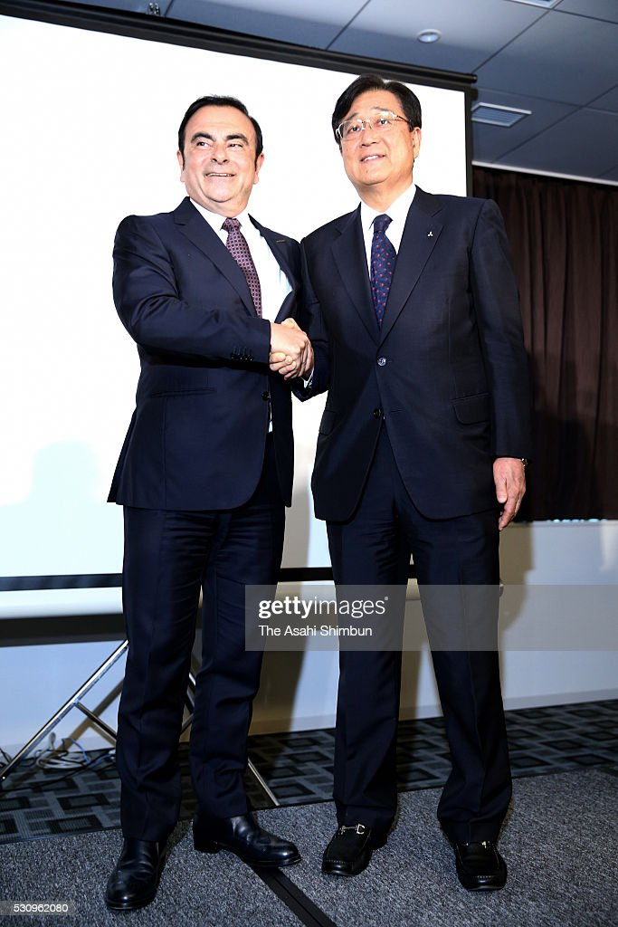 Nissan Motor Co President Carlos Ghosn (L) and Mitsubishi Motors Chairman Osamu Masuko (R) shake hands during a joint press conference at TKP Garden City Yokohama on May 12, 2016 in Yokohama, Kanagawa, Japan. Nissan will take 34 percent stake in troubled Mitsubishi Motors, for 237 billion Japanese yen (approximately 2.2 million U.S. dollars) and become the top shareholder in the automaker, which has been troubled by fuel economy scandal.