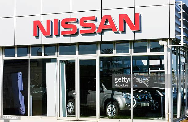 nissan sign and suvs at car dealership showroom - nissan stock pictures, royalty-free photos & images