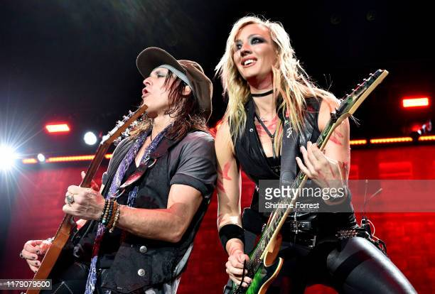 Nita Strauss and Ryan Roxie perform with Alice Cooper on stage at Manchester Arena on October 04, 2019 in Manchester, England.