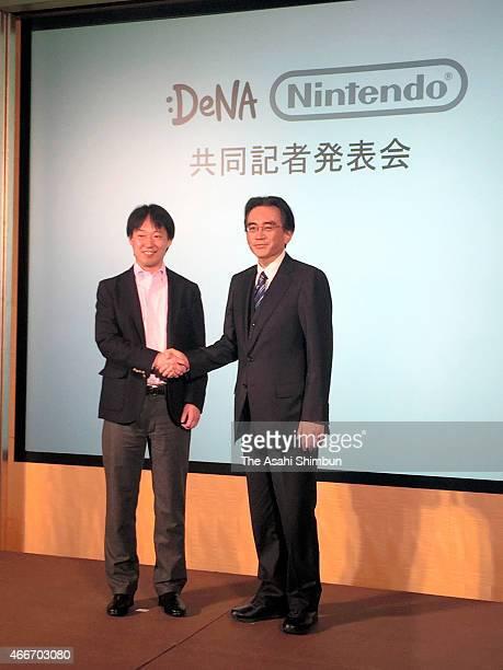 Nitendo President Satoru Iwata and online game company DeNA president Isao Moriyasu shake hands during a press conference on March 17 2015 in Tokyo...