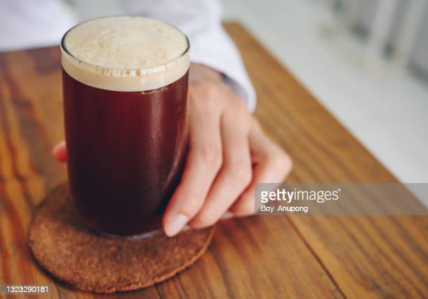 a nitro cold brew coffee on the wood table in cafe shop. - 職業 ポーター ストックフォトと画像