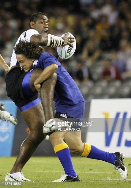Niue's Poimatagi Okesene tries in vein to tackle Fiji's Norman Ligairi in their Group A Rugby 7's match in the preliminary round of the 2006...