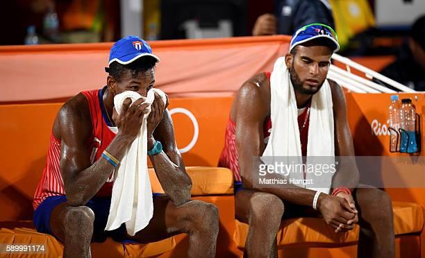 Nivaldo Nadhir Diaz Gomez and Sergio Reynaldo Gonzalez Bayard sit dejected after losing the Men's Beach Volleyball Quarterfinal match between the...