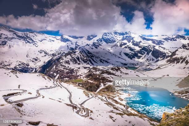 passo nivolet - strada di montagna e paesaggio ghiacciato del lago agnel - gran paradiso, italia - parco nazionale del gran paradiso foto e immagini stock