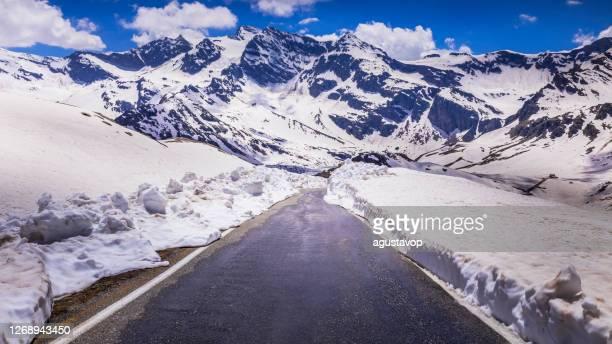 passo nivolet: strada di montagna tra neve - dolomiti, gran paradiso, alpi graie - italia - parco nazionale del gran paradiso foto e immagini stock