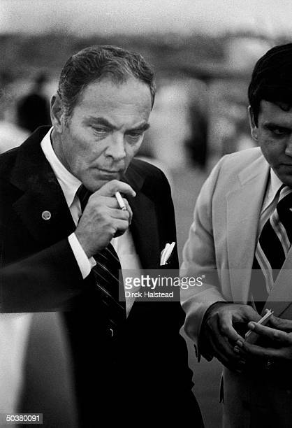 Nixon aide Gen Alexander Haig smoking a cigarette and looking pensive upon his arrival with Pres Nixon at the Phoenix Sky Harbor Airport prior to...