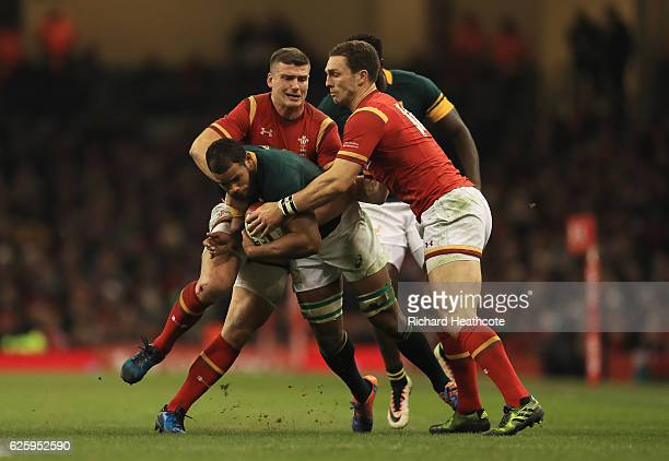 Nizaam Carr of South Africa is tackled by Scott Williams and George North of Wales during the international match between Wales and South Africa at...