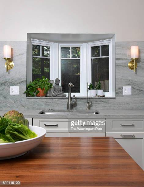 Nizam Ali coowner of Ben's Chili Bowl has a bay window over the sink and quartzite counters that continue up the wall as a extended backsplash...