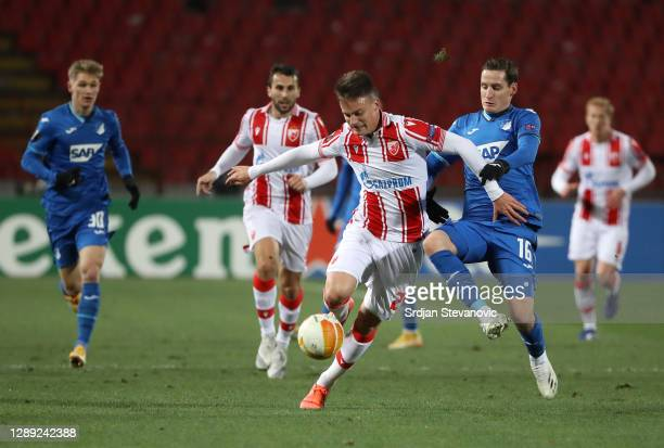 Njegos Petrovic of Crvena Zvezda is challenged by Sebastian Rudy of TSG 1899 Hoffenheim during the UEFA Europa League Group L stage match between...
