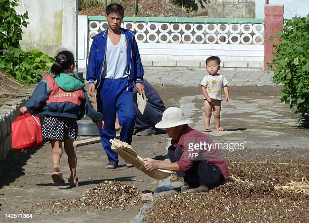 NKoreapoliticseconomysuccessionFEATURE by Ian Timberlake This photo taken on September 23 2010 shows residents drying crops outside their homes at a...