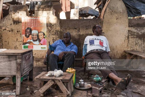 'nMalian man of whom one of them is wearing a tee shirt depicting a France flag are seen sitting next to a poster of Presidential election candidate...