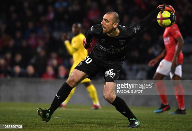 Nîmes' French goalkeeper Paul Bernardoni passes the ball during the French L1 football match between Nimes Olympique and FC Nantes at the Costieres...