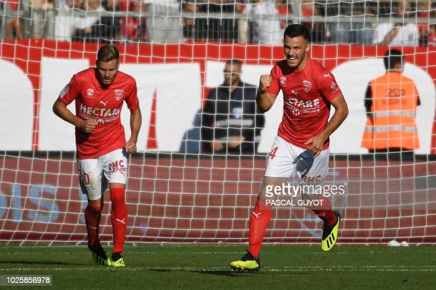 Nîmes' French midfielder Antonin Bobichon celebrates after scoring their first goal past Nîmes' French forward Renaud Ripart during the French L1...