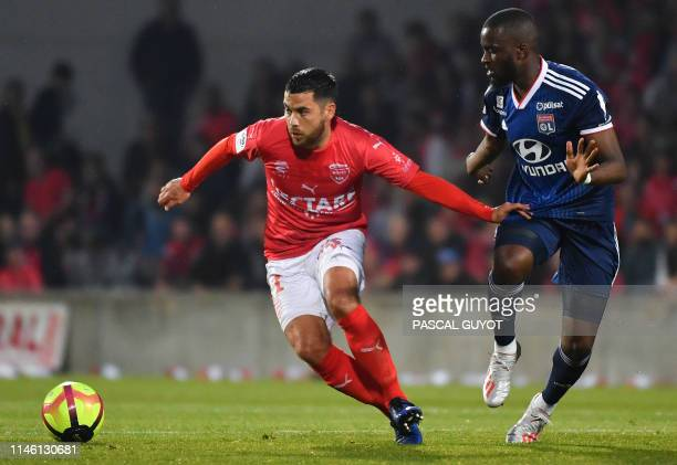 Nîmes' French midfielder Teji Savanier fights for the ball with Lyon's French forward Tanguy NDombele Alvaro during the French L1 football match...