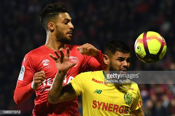 Nîmes' Gabonese midfielder Denis Bouanga heads the ball with Nantes' Brazilian defender Lima during the French L1 football match between Nimes...