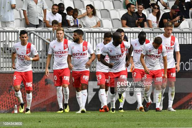 Nîmes' players celebrate after they scored during the French L1 football match between FC Girondins de Bordeaux and Nimes Olympique on September 16...