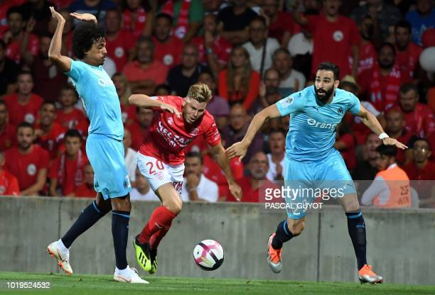Nîmes's French forward Renaud Ripart fights for the ball with Olympique Marseille's French defender Adil Rami and Olympique Marseille's Brazilian...