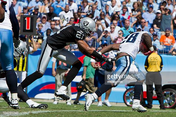 Nnamdi Asomugha of the Oakland Raiders pulls down the pants of Chris Johnson of the Tennessee Titans during the season opener at LP Field on...