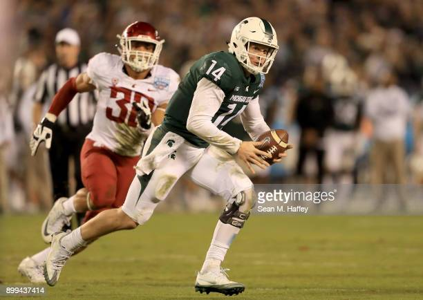 Nnamdi Oguayo of the Washington State Cougars pressures Brian Lewerke of the Michigan State Spartans from the pocket during the second half of the...
