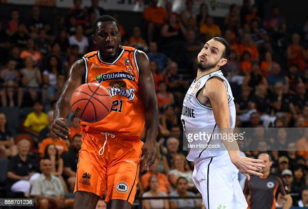 Nnanna Egwu of the Taipans contests the ball with Chris Goulding of Melbourne United during the round nine NBL match between the Cairns Taipans and...