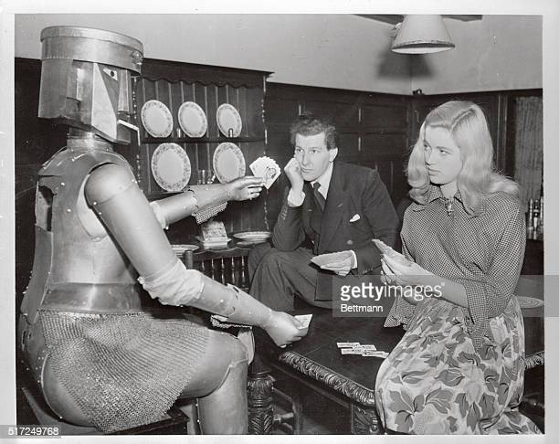 'No cheating please' Robert cautions as he sits down for a friendly hand with his bosses Denis Hamilton and pretty Diana Dors After dinner dishes are...