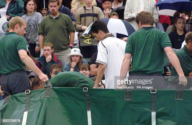 British No.1 Tim Henman leaves Court One after rain interrupted play for the second time during his quarter final match against Cedric Pioline of...