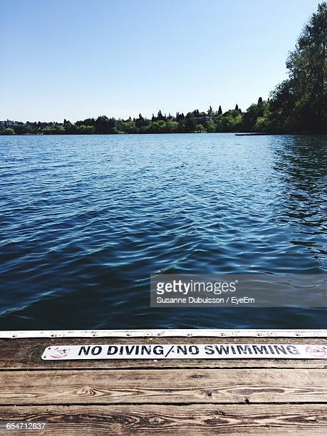 No Diving Sign On Jetty Over Lake Against Clear Sky