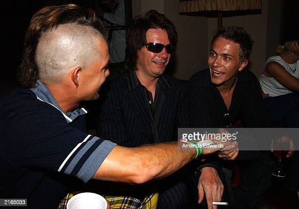 'No Doubt' drummer Adrian Young chats with guitarist Andy Taylor and his son Andy Jr at an afterparty at the Chateau Marmont on July 15 2003 in...