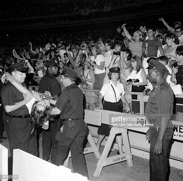 No doubt overcome by the soulful renderings this teenager is carried off after fainting during the Beatles concert at Shea Stadium