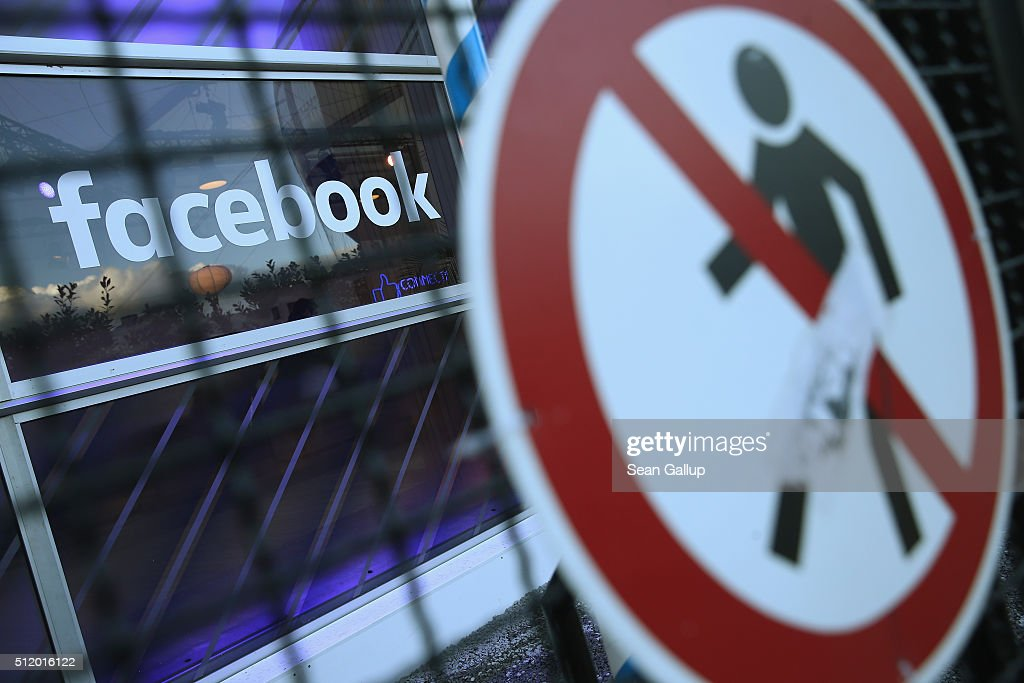 A no entry symbol hangs on an opened gate next to the Facebook logo at the Facebook Innovation Hub on February 24, 2016 in Berlin, Germany. The Facebook Innovation Hub is a temporary exhibition space where the company is showcasing some of its newest technologies and projects.