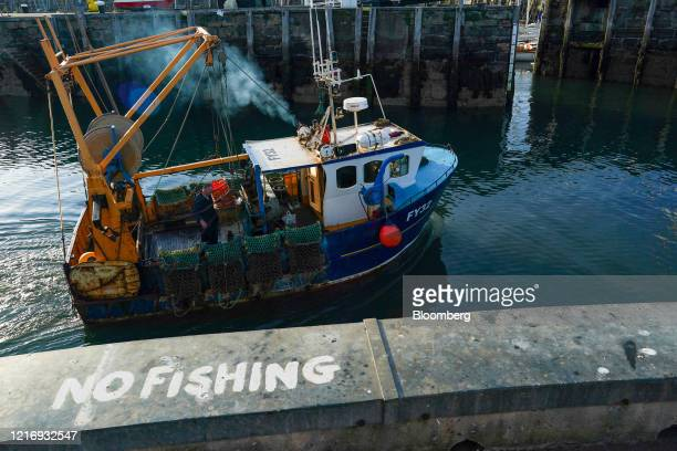A 'No Fishing' sign sits on the quayside as a fishing boat heads out to sea from the harbour in Scarborough UK on Tuesday June 2 2020 The threat of a...