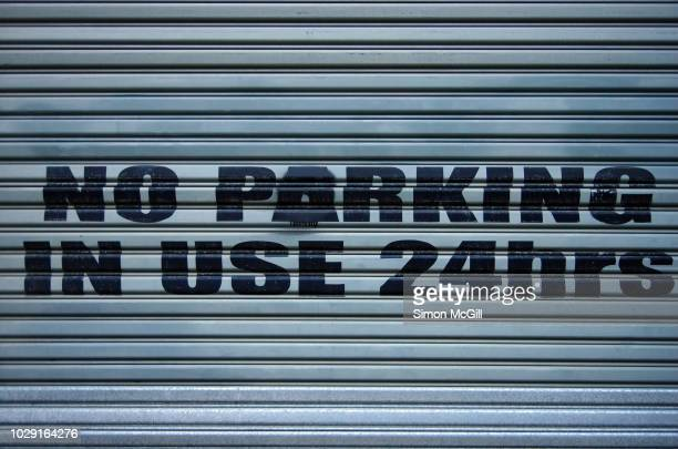 'no parking: in use 24 hours' sign painted on a metal roller shutter garage door - industrial door stock pictures, royalty-free photos & images