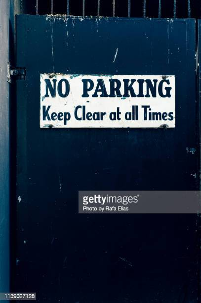 """""""no parking"""" sign on old door - road sign board stock pictures, royalty-free photos & images"""
