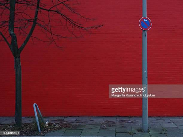 No Parking Sign On Pole Against Red Wall