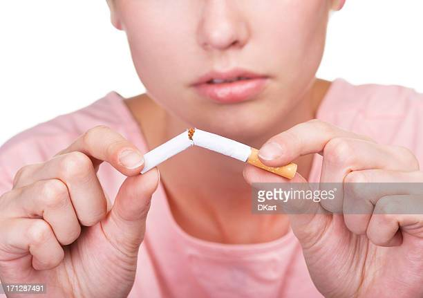 No smoking concept. Young woman breaking cigarette