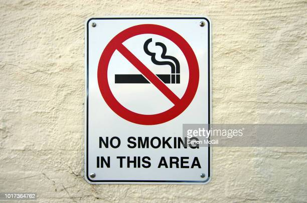 'no smoking in this area' sign on a building exterior stucco brick wall - no smoking sign stock pictures, royalty-free photos & images
