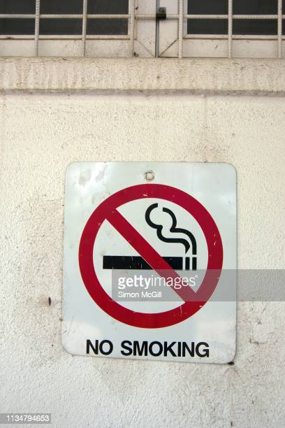 'No smoking' sign on the exterior wall of a building
