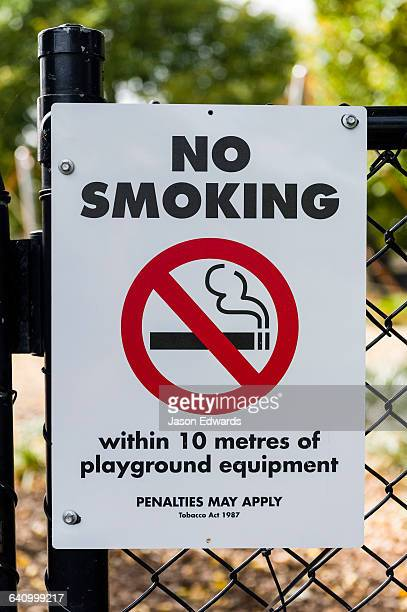 A no smoking sign on the fence of a childrens playground.