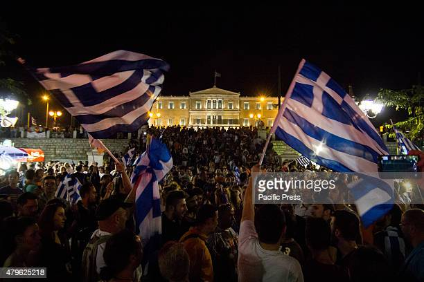 """No"""" supporters wave Greek flags. People gathered in Syntagma Square to celebrate the """"No' result, that gives them hope to achieve a better result to..."""
