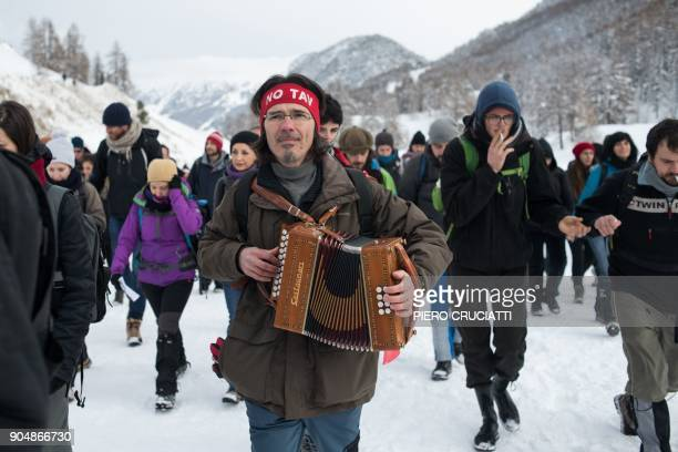 A 'No Tav' activist plays an harmonium during a 'Briser les frontieres' activist group march between Claviere Italy and Montgenevre France in support...