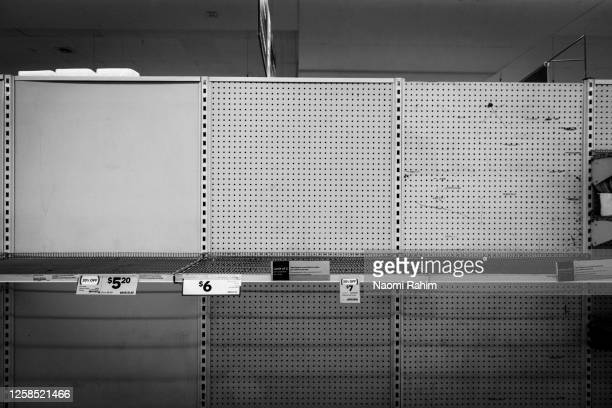 no toilet paper or hand sanitiser - empty supermarket shelf due to panic buying during covid-19 pandemic - panic buying stock pictures, royalty-free photos & images