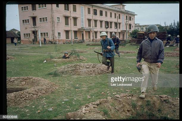 No Vietnamese militia during air raid drill running across field riddled w bomb craters w bombed out bicycle factory in background