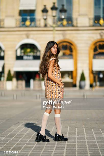 Noa Souffir wears a Gucci dress with printed orange and brown chains and a white large collar, white high mesh socks, black leather shoes, on October...