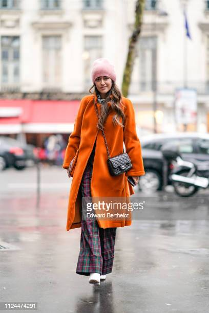 Noa Souffir wears a pink beanie hat an orange coat a Chanel bag checked flared pants white shoes during Paris Fashion Week Haute Couture Spring...