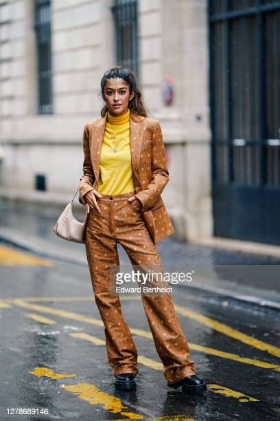 Noa Souffir wears a yellow turtleneck pullover, a brown blazer jacket, suit flared pants, a Prada pale pink bag, black leather shoes, outside Paul &...