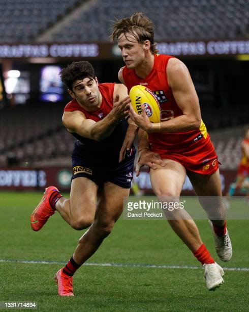 Noah Anderson of the Suns and Christian Petracca of the Demons contest the ball during the round 20 AFL match between Gold Coast Suns and Melbourne...