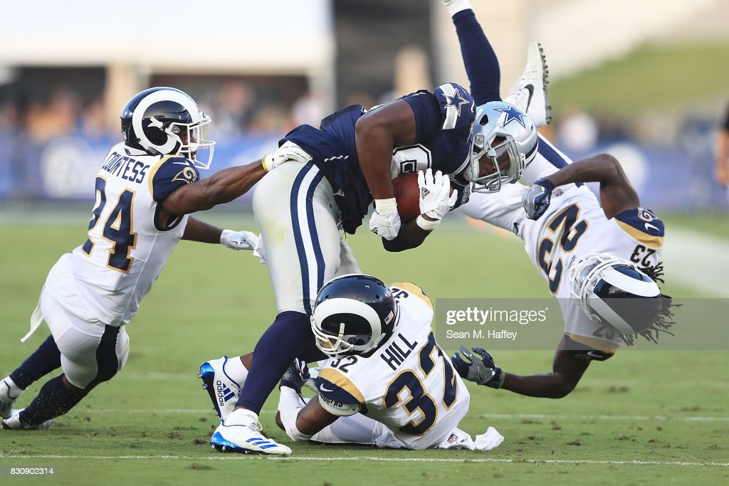 Noah Brown #85 of the Dallas Cowboys catches the short pass and gets tackled by Troy Hill #32, Nickell Robey-Coleman #23, and Blake Countess #24 of the Los Angeles Rams at Los Angeles Memorial Coliseum on August 12, 2017 in Los Angeles, California.