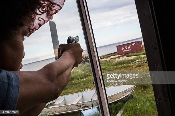 Noah Carl plays with guns while hanging out at his friend's house on July 3 2015 in Newtok Alaska Newtok is one of several remote Alaskan villages...