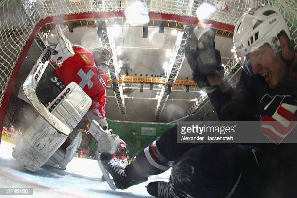 Noah Clarke of the US crashes against Reto Berra , goalie of Switzerland during 4th match of the German Ice Hockey Cup 2011 between Switzerland and...